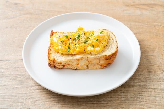Torrada de pão com ovo mexido no prato branco