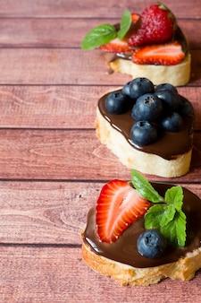 Torrada de pão com pasta de chocolate e morangos mirtilos hortelã na mesa