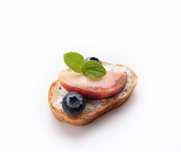Torrada de pão com pêssego e baga azul sobre fundo branco isolado