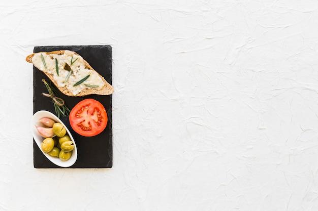 Torrada de pão com queijo, alecrim, tomate e tigela de azeitona na placa de ardósia