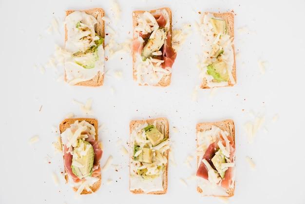 Torrada de pão com queijo ralado; fatia de abacate e presunto em pano de fundo branco