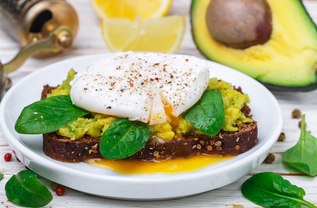 Torrada de pão de centeio com coentro, ovo escalfado com espinafre de salada verde