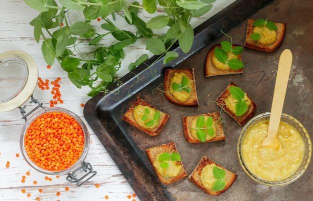 Torrada de pão delicioso com hummus (patê, macarrão, molho) de lentilhas e cenouras com brotos de ervilha,