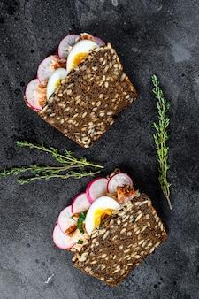 Torrada de pão integral com salmão defumado quente, ovo e rabanete