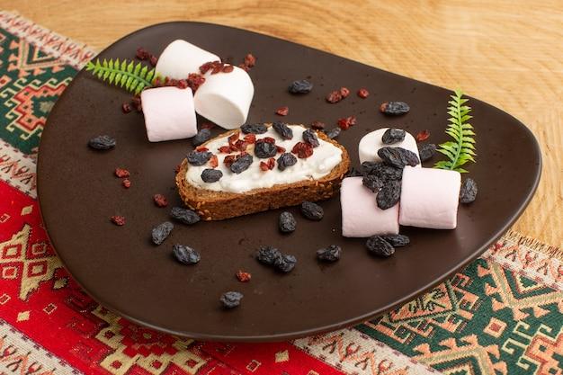Torrada de pão junto com marshmallows e frutas secas em prato escuro sobre madeira