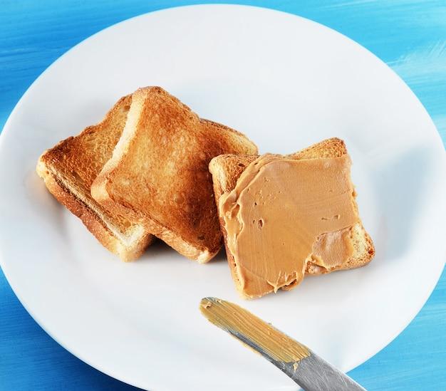 Torrada de pão torrado com manteiga de amendoim e um prato
