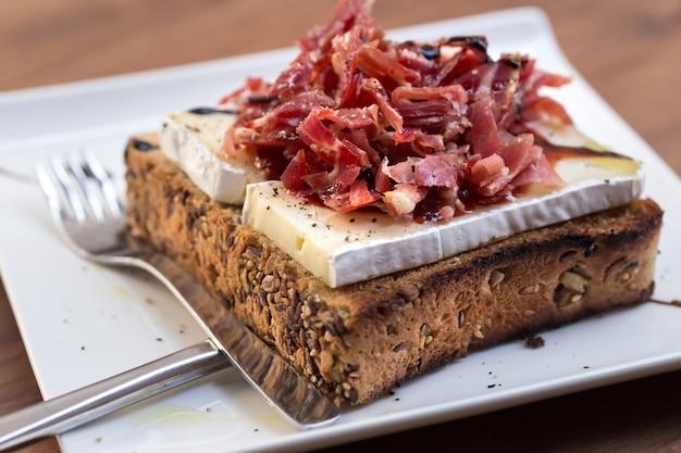 Torrada de presunto serrano, queijo brie e marmelada de tomate.