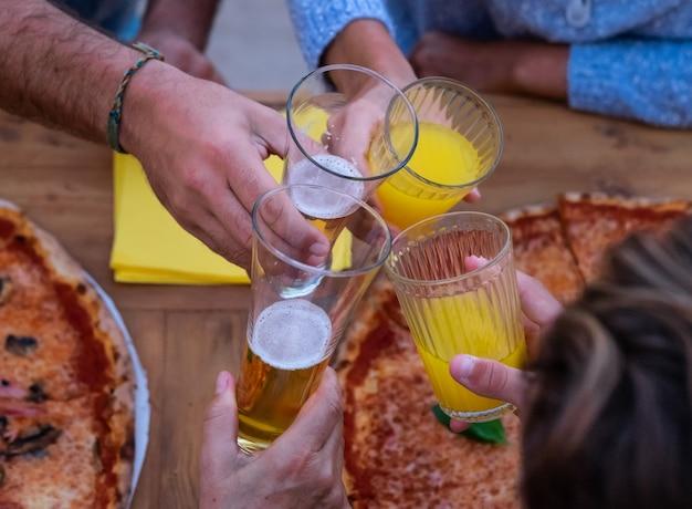 Torrada de quatro mãos com cerveja e suco de laranja caucasianos dividem uma pizza grande