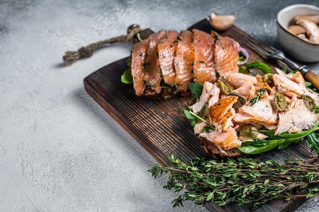 Torrada de sanduíche com salmão defumado quente e frio, rúcula e cream cheese em uma tábua de madeira