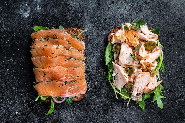 Torrada de sanduíche com salmão defumado, rúcula e cream cheese. fundo preto. vista do topo.