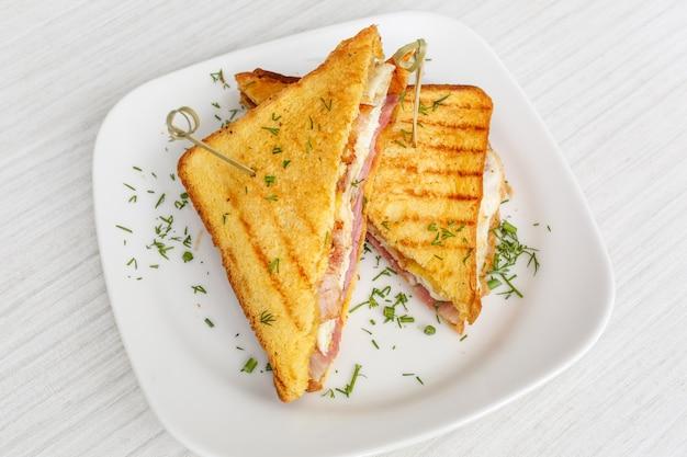 Torrada de sanduíche grelhada com queijo, bacon e salada na mesa de madeira branca, superfície