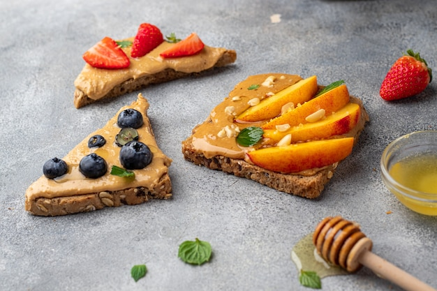 Torrada de sanduíches de amendoim com mel, hortelã, mirtilo, nectarina e morango