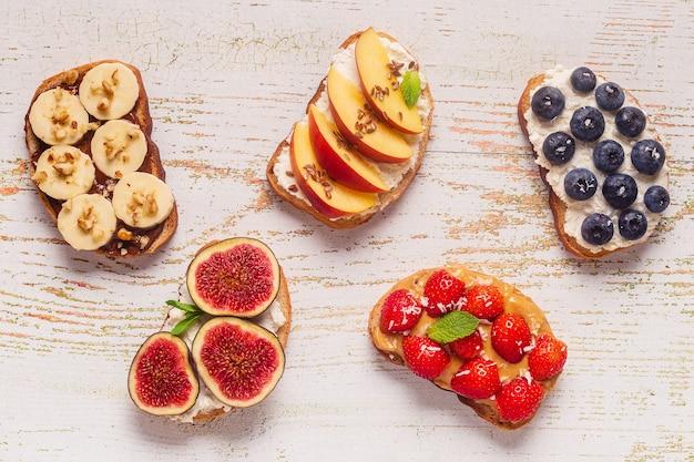 Torrada de verão caseira com cream cheese, manteiga de amendoim e frutas e bagas, vista superior.
