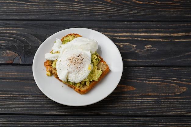 Torrada e ovo escalfado com abacate em um prato na mesa de madeira