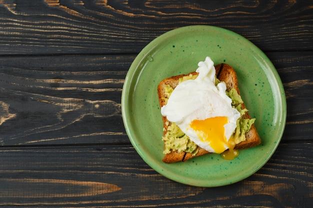 Torrada e ovo escalfado com abacate em uma placa verde na mesa de madeira