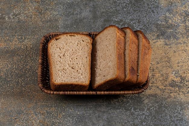 Torrada fatiada de pão de centeio em cesta de madeira