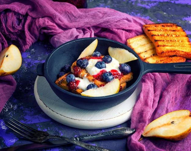 Torrada francesa com frutas, xarope e creme de leite em uma frigideira preta de ferro fundido