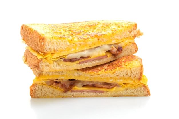 Torrada francesa, presunto, bacon, queijo, sanduíche com ovo isolado no fundo branco