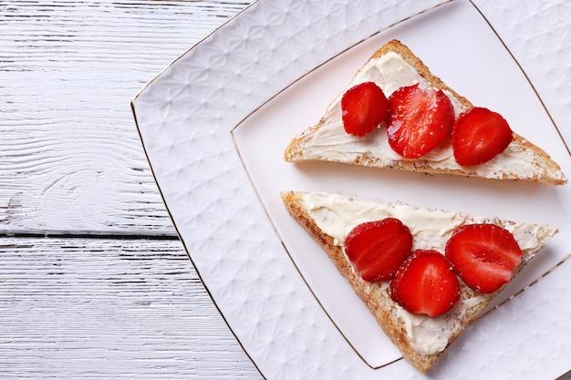 Torrada fresca com manteiga caseira e morango fresco no prato na mesa de madeira