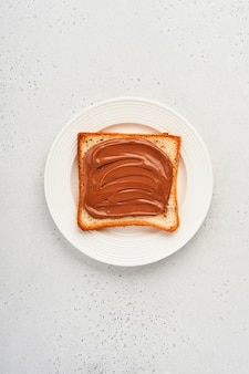 Torrada fresca com pasta de chocolate em um prato branco sobre fundo cinza