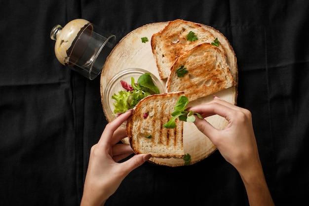Torrada frita com uma lata de patê em uma bandeja de madeira