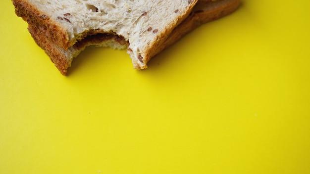 Torrada mordida em fundo amarelo - sanduíche com pasta de chocolate. plano de fundo para o café da manhã. vista de cima - copie a fotografia do espaço.