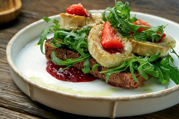 Torradas apetitosas com queijo de cabra, geléia vermelha, rúcula e morangos com pão de centeio em um prato em um de madeira