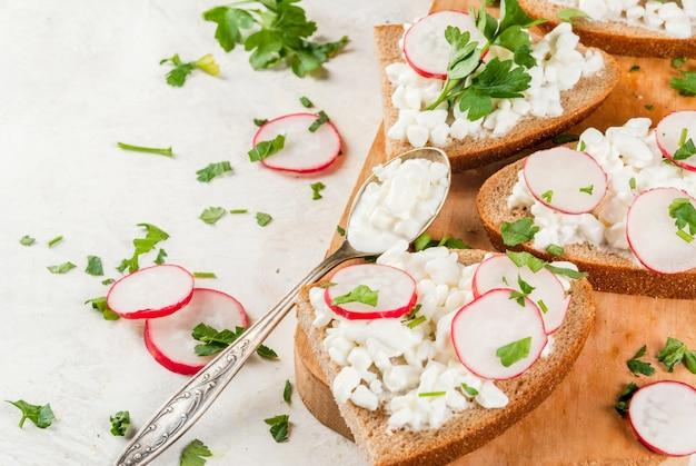 Torradas caseiras de sanduíche com queijo cottage, rabanete e salsa na mesa branca, copie o espaço