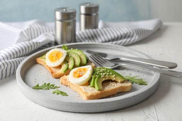 Torradas com abacate e ovo, talheres e toalha em branco, closeup