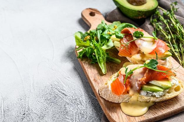 Torradas com abacate e salmão defumado. fundo branco.