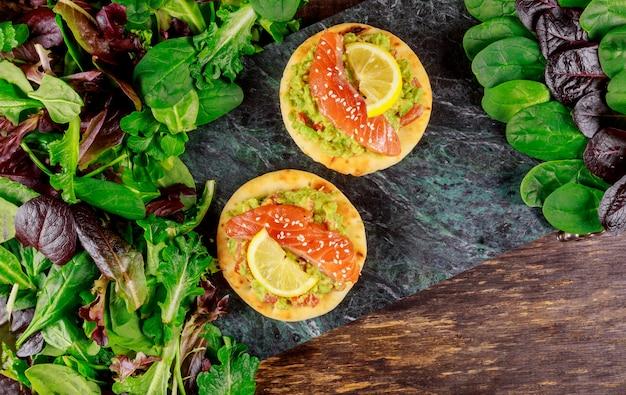 Torradas com abacate salmão defumado e salada verde