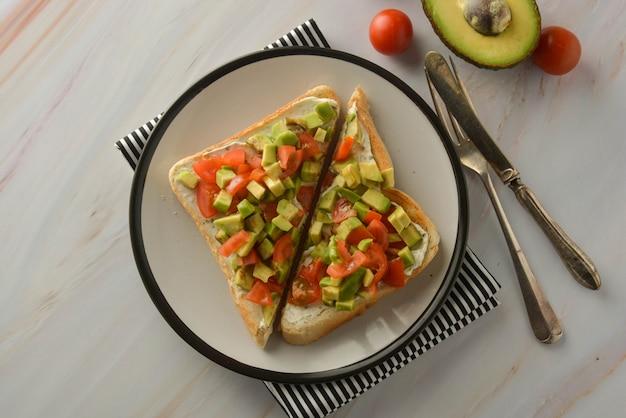 Torradas com cream cheese, abacate e tomate cereja. comida saudável. copie o espaço.