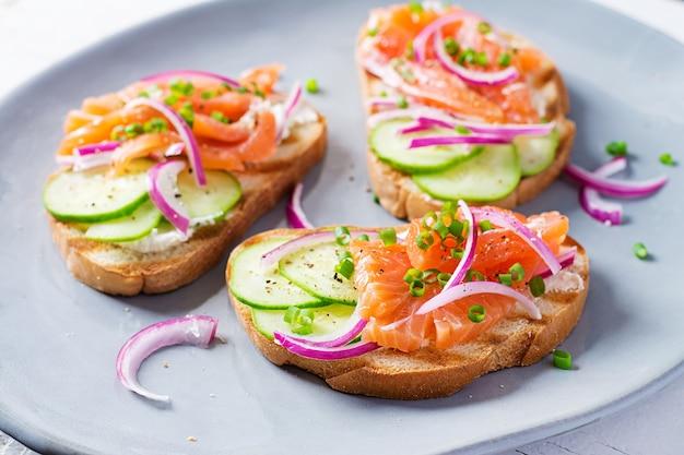 Torradas com cream cheese, salmão defumado, pepino e cebola roxa na mesa de madeira rústica. sanduíches abertos. cuidado saudável, conceito de superalimento.