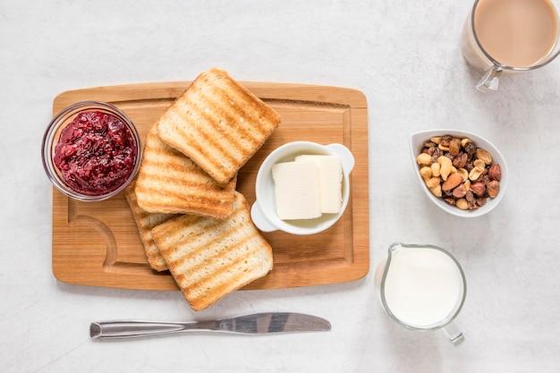 Torradas com manteiga e marmelada na placa de madeira