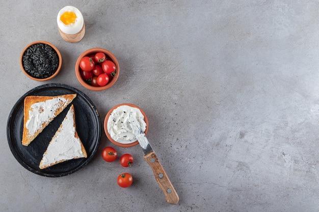 Torradas com manteiga e tomate cereja vermelho colocadas sobre fundo de mármore.