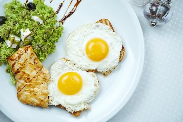 Torradas com ovos fritos, filé de frango grelhado, salada com queijo feta e azeitonas em chapa branca.