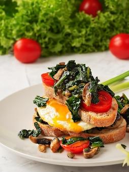 Torradas com ovos mexidos no pão torrado com espinafre, cogumelos e tomate em um prato cinza. fechar-se. ovo frito no café da manhã.