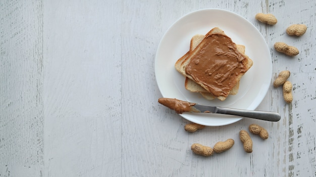 Torradas com pasta de amendoim em uma superfície branca