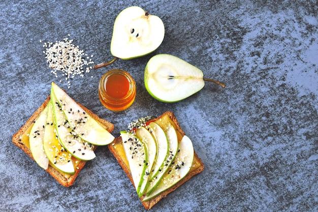 Torradas com pêra, queijo e mel. lanche saudável. keto café da manhã. keto almoço. sanduíche aberto vegetariano com pêra e queijo. bruschetta com queijo, pêra e mel.