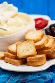 Torradas com queijo, azeitonas e pimenta vermelha em prato branco