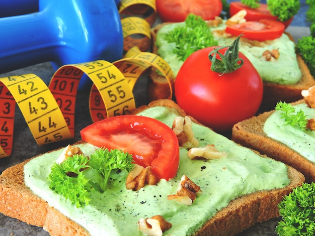 Torradas com queijo cottage verde e nozes e tomate. fita métrica. halteres. comida de fitness.
