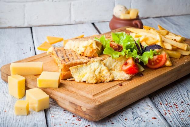 Torradas com queijo e tomate e batata frita no prato