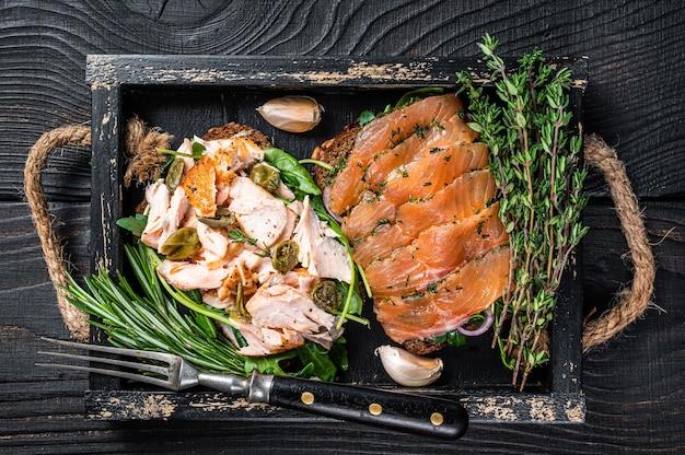 Torradas com salmão fumado quente e frio, rúcula em tabuleiro de madeira com ervas aromáticas.