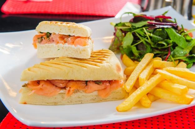 Torradas com salmão vermelho servidas com batata frita e salada