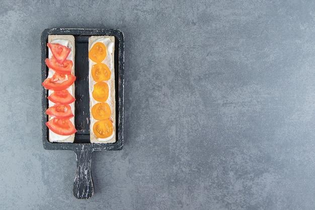 Torradas crocantes com tomate na placa de madeira.