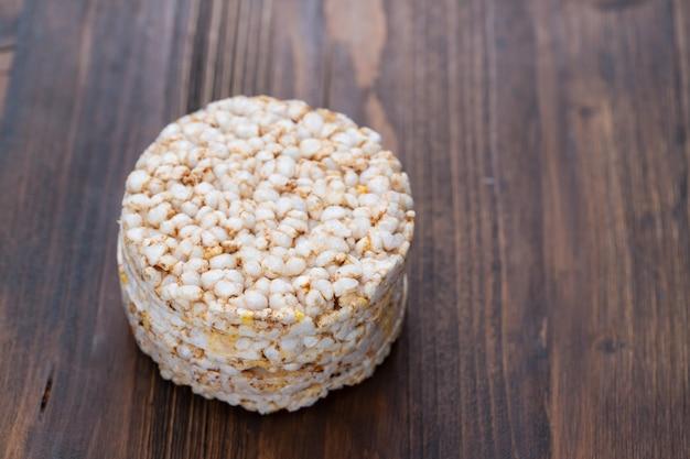 Torradas crocantes de dieta de arroz em superfície de madeira