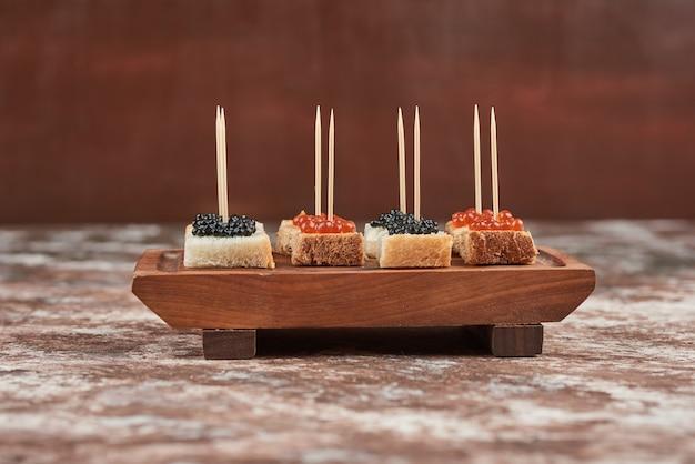 Torradas de aperitivo com caviar em tábua de madeira.