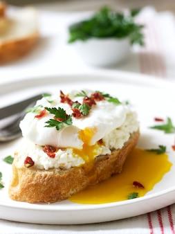Torradas de baguete crocante com queijo cottage, ovo escalfado e tomate seco sobre um fundo claro.
