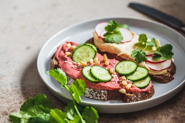 Torradas de beterraba e hummus clássico. conceito de comida vegan.