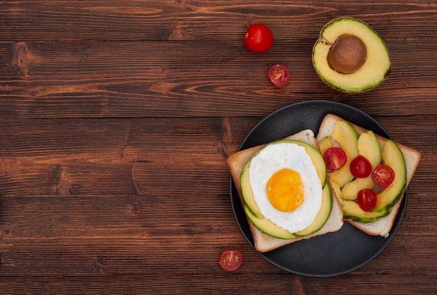 Torradas de café da manhã saudável com abacate e ovo frito no plano de fundo de madeira marrom